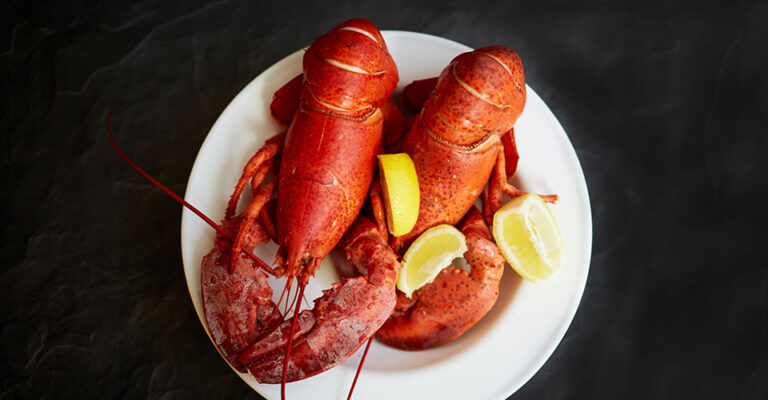 two lobsters on a white plate with lemon wedges