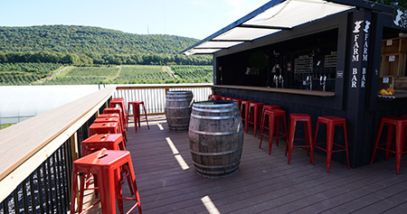 outdoor bar and red chairs on deck overlooking orchard