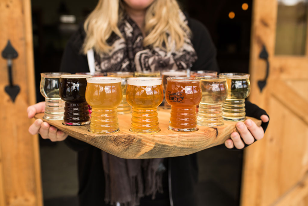 girl holding glasses of cider on a wooden board
