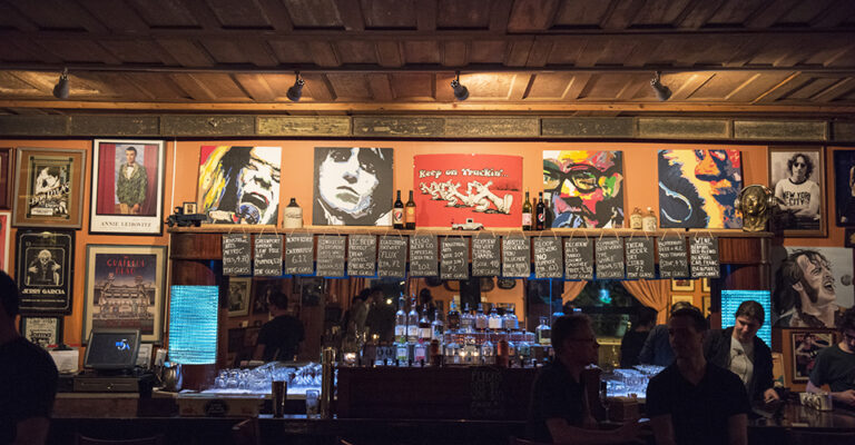 view of dark bar with music posters on wall