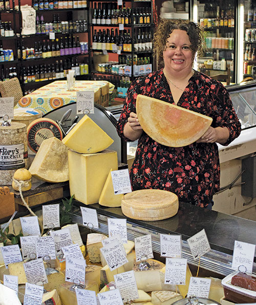 woman holding large wheel of cheese in cheese shop