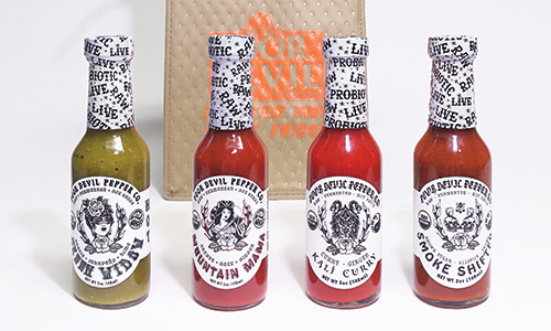 four bottles of hot sauce in front of beige tote bag