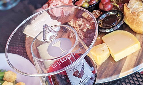 galss of wine with plastic cover and charcuteries board in background
