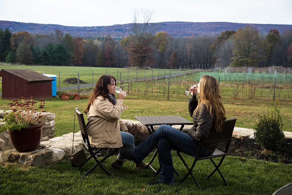 two women sipping wine at table with mountain view in background
