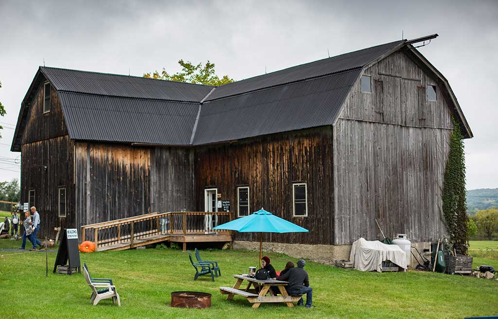 brown barn with picnic table in foreground