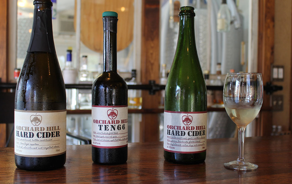 three bottles and glass on wood bar