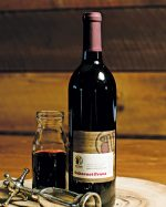 Bottle of red wine with vintage corkscrew on wood trivet
