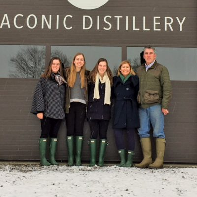 four women and a man in front of brown distillery door
